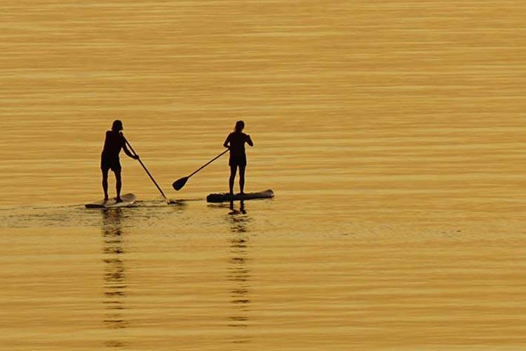 Over ons headerfoto, twee personen aan het peddelen op het water.