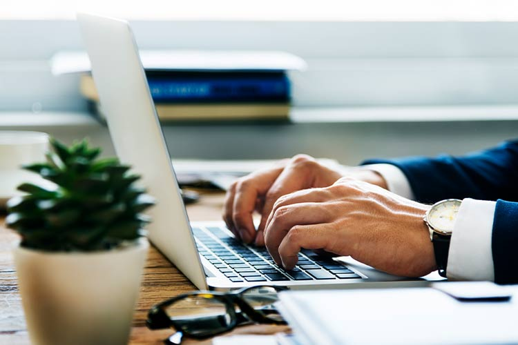 Man in business suit typing blog for entrepreneurs on laptop