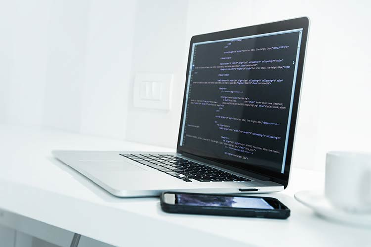 professionele websites - laptop met css code - Marketing Spectrum