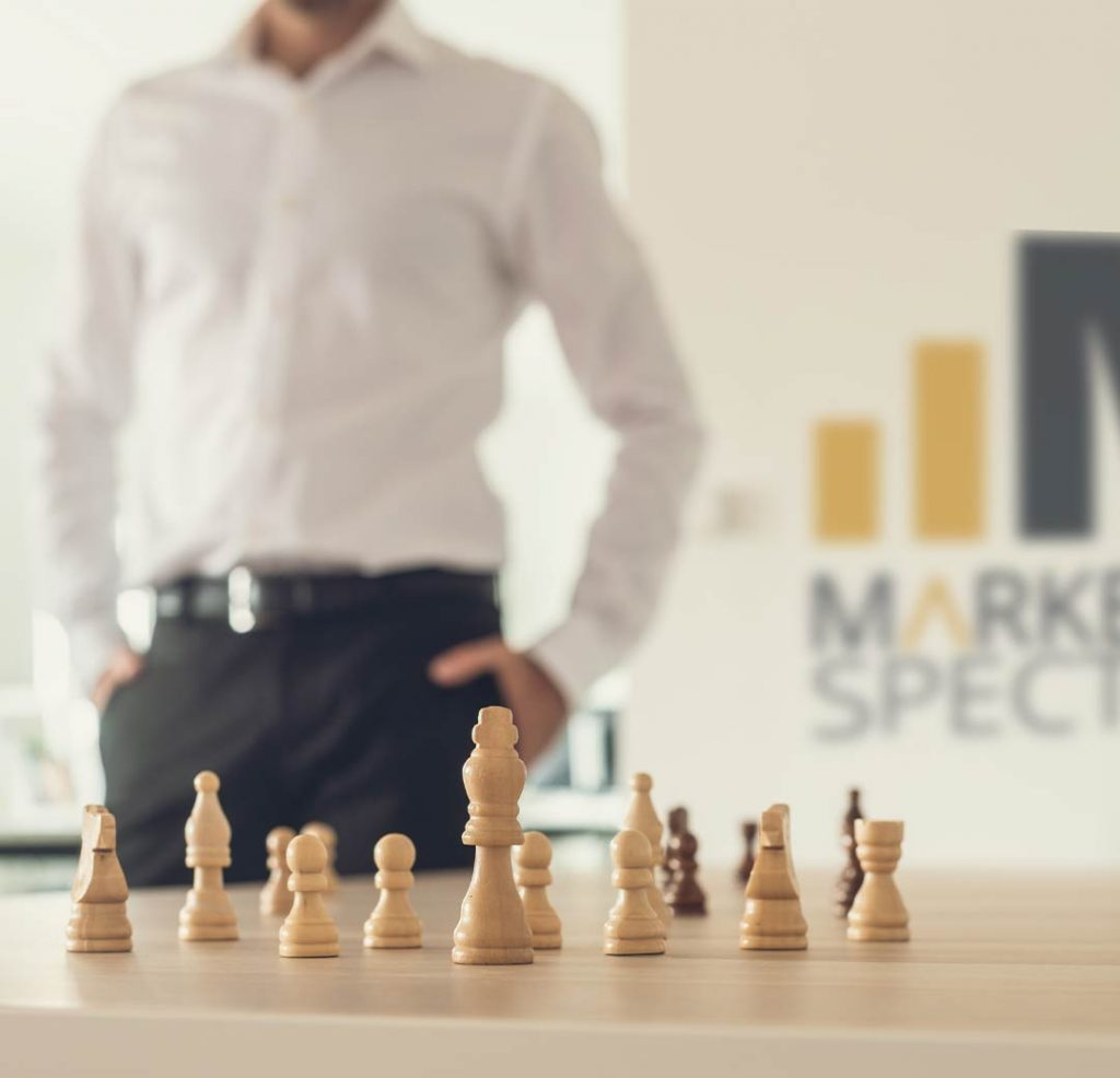Man standing behind chessboard next to marketing spectrum website agency online marketing agency logo